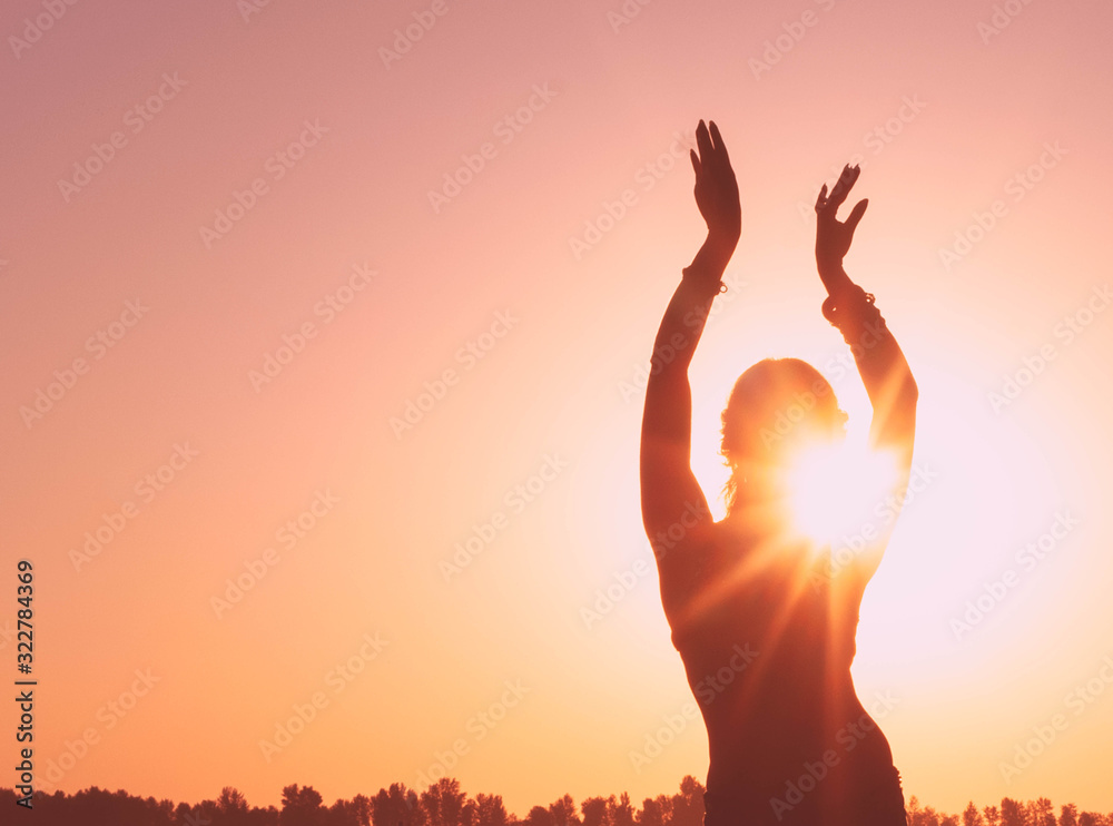 Fototapeta dark glowing silhouette of slim woman with hands up in the air illuminated with sunshine dancing traditional tribal belly dance in front of aurora sky at sunrise