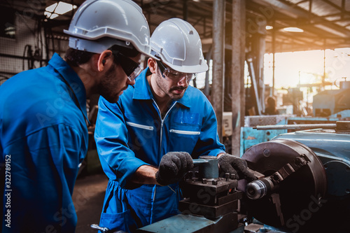 The Industry engineering wearing safety uniform control operating lathe grinding machine working in industry factory Canvas Print