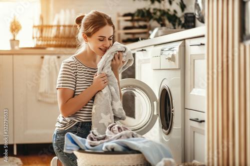 Obraz na płótnie Happy housewife woman in laundry room with washing machine  .