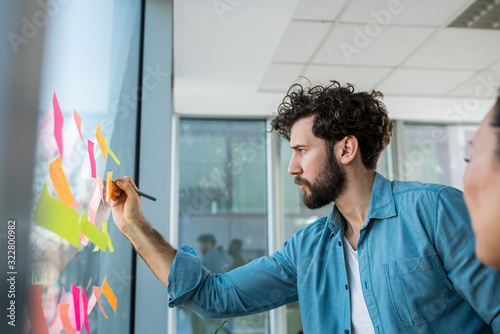 Obraz A young creative man brainstorming ideas for the upcoming project. He pasted sticky notes on a window and writes on them. - fototapety do salonu