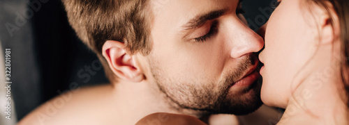 Obraz na plátně panoramic shot of handsome boyfriend with closed eyes kissing girlfriend