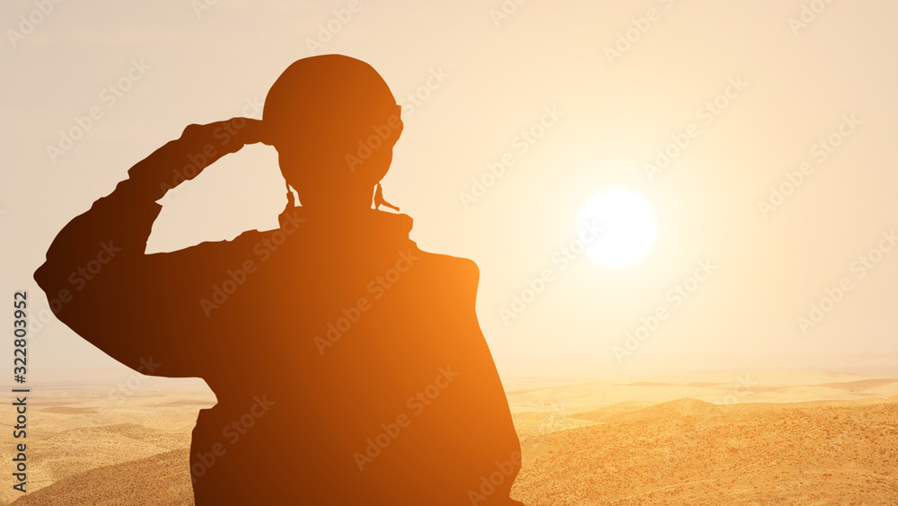 Fototapeta Silhouette Of A Solider Saluting Against the Sunrise in the desert of the Middle East. Concept - armed forces of UAE, Israel, Egypt