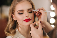 Makeup Artist Applies Eye Shadow, Perfect Evening Makeup. Beauty Blond Hair Girl With Perfect Skin And Red Lipstick