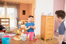 Down Syndrome Boy Playing With Toys At Dining Table