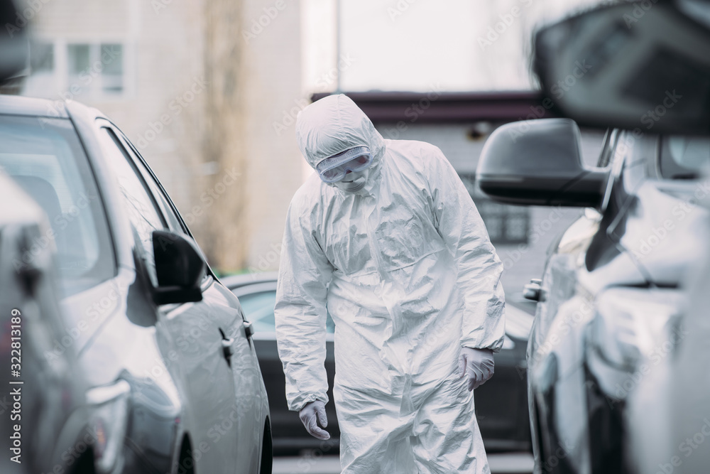 Fototapeta selective focus of asian epidemiologist in hazmat suit and respirator mask inspecting vehicles on parking lot