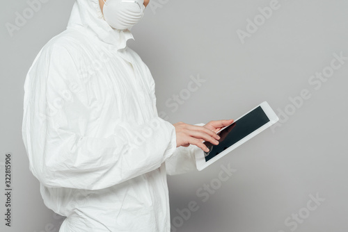 Fototapeta cropped view of epidemiologist in hazmat suit and respirator mask holding digital tablet with blank screen on grey background obraz