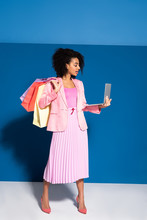 Elegant African American Businesswoman With Shopping Bags Using Laptop On Blue Background