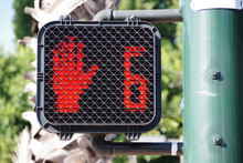 Pedestrian Crosswalk Traffic Signal At A City Intersection With A Red Hand Warning To Not Enter Because Only Six Seconds Left For Crossing