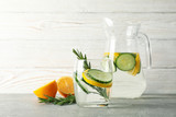 Jug and glass with cucumber water on grey table, close up