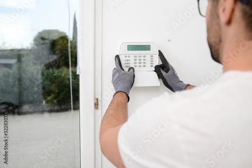Wallpaper Mural handsome man worker installing alarm technology insurance in home for burglar pr