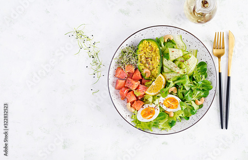 Fototapeta Ketogenic diet breakfast. Salt salmon salad with greens, cucumbers, eggs and avocado. Keto/paleo lunch. Top view, overhead obraz