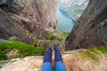 Two Feet With Hiking Boots On Them Hanging Down From A Steep Cliff With A View On Stunning Lysefjorden Shimmering With Many Shades Of Blue And Green. View From Preikestolen. Clear And Bright Day.