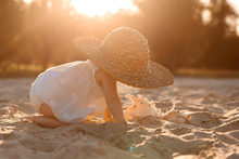 Baby Girl In White Clothes And A Straw Hat Sits On The White Sand On The Beach In Summer