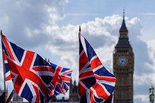 Big Ben At The Palace Of Westminster With Union Jack Flags In The Foreground