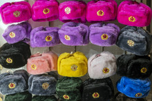 Military Caps Of Different Colors With The Coats Of Arms Of Russia And The USSR As Souvenirs From Moscow. Rows Of Russian Winter Hats Of Different Colors With Army Emblems At The Street Market