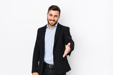 Young Caucasian Business Man Against A White Background Isolated Stretching Hand At Camera In Greeting Gesture.