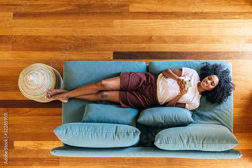 Obraz Black woman chatting on smartphone lying on couch at home - fototapety do salonu