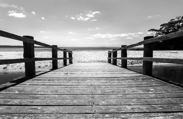 Fototapeta Morze Black and white photo of a wooden bridge to the ocean, Jervis Bay Australia