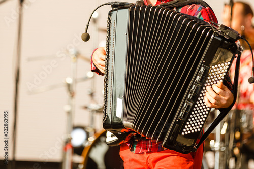 Male playing on the accordion against a grunge background Wallpaper Mural