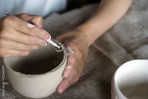 Female hands hold a bowl for casting clay products Fototapeta