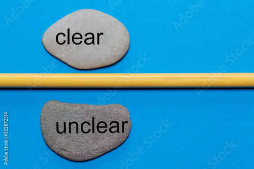 Valokuvatapetti The words clear and unclear are written on natural smooth stones separated by a yellow pencil