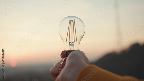 Photo Close up hands woman holds a house light bulb at sunset renewable energy nature