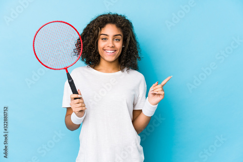Photo Young african american woman playing badminton smiling and pointing aside, showing something at blank space