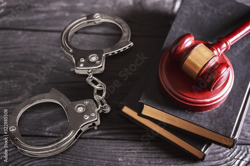 Fototapeta Wooden judge hammer with handcuffs and books on the desk obraz