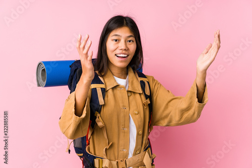 Photo Young chinese traveler woman isolated receiving a pleasant surprise, excited and raising hands