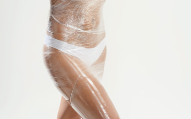 Body wrapping in a spa room. Anti cellulite fat burning procedure in massage salon for perfect slim body and clear skin. Wellness center concept