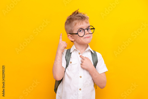 Back to school. Portrait of funny clever blonde school boy in round glasses with bag in white shirt. Pointing up. Yellow studio background. Education. Looking and smiling at camera
