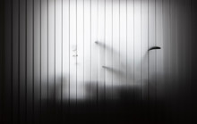 Vertical White Blinds Are Closed. Against The Background, Flowers Standing On The Windowsill Are Partially Translucent.