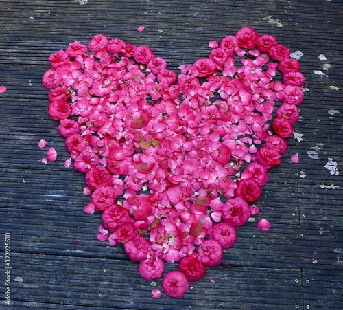 Closeup shot of a romantic hear made with rose petals on a wooden surface - Valentine concept