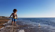 Small Boy Throw Stones To Sea