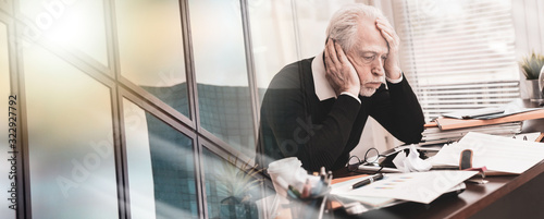 Overworked businessman sitting at a messy desk; multiple exposure Wallpaper Mural