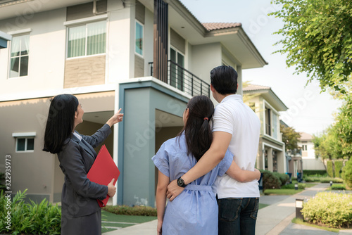 Asian woman Real estate broker agent showing a house project detail in her file to the young Asian couple lover looking and interest to buy it Canvas-taulu