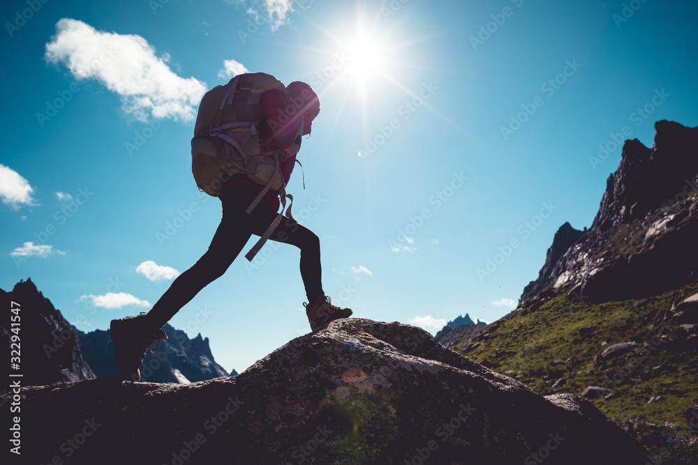 Fototapeta Successful woman hiker hiking in sunrise mountains