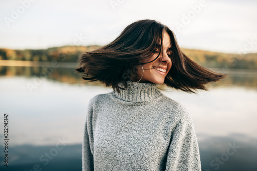 Fotografie, Tablou Close-up outdoor portrait of happy young brunette woman with closed eyes with blowing hair, wearing grey sweater, posing on nature background