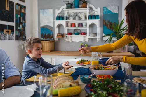 mother serving food to her son, family gathering