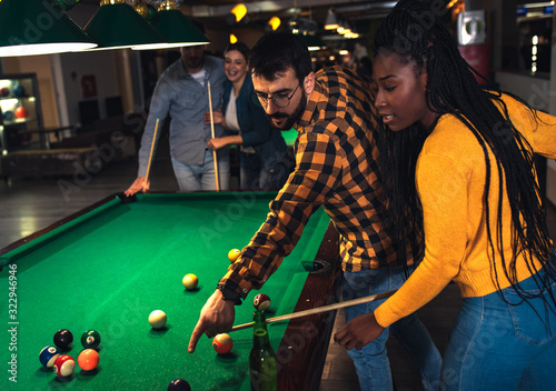 Fotografie, Obraz Group of cheerful friends playing billiard together in bar.