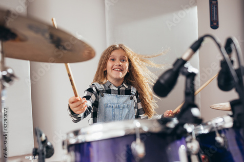 young girl playing drums in music studio - 322949172