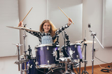 Young Girl Playing Drums In Mu...