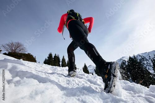 Trail runner woman running in winter mountains on snow Wallpaper Mural