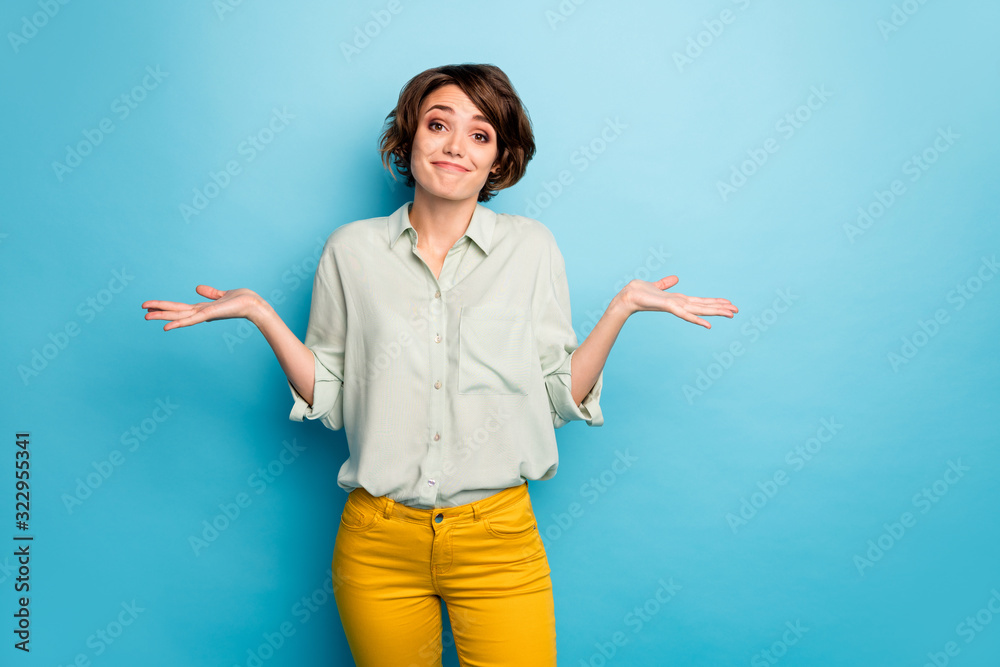 Fototapeta Photo of pretty lady raise hands shrug shoulders do not care friends problems ignoring smile wear casual green shirt yellow trousers isolated blue color background