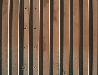 Background picture of rusty metal wall panels on a sunny day