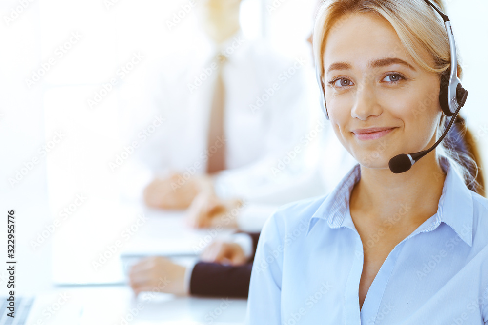 Fototapeta Group of diverse phone operators at work in sunny office. Handsome business woman with headphones consulting clients. Call center and business people concept