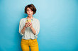 Photo of attractive lady hold telephone hands read new blog post comments not believe eyes speechless wear casual green shirt yellow trousers isolated blue color background