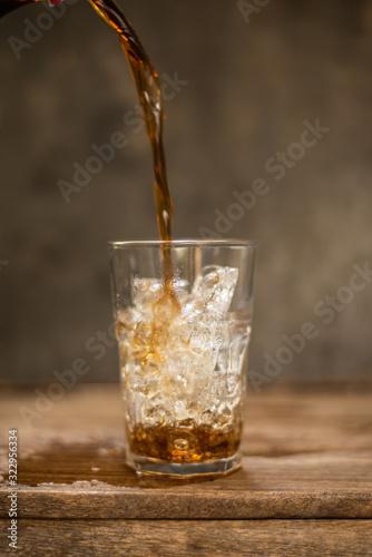 Photo Soft drink splashing on wood table.