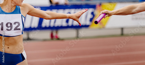 Fotografiet women relay team passing of baton in track and field
