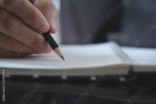 Fototapety, obrazy: Businessman writing on notebook
